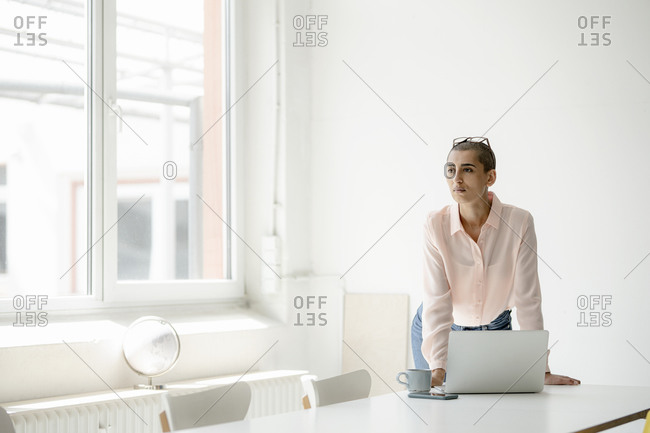 Businesswoman with laptop at desk in loft office