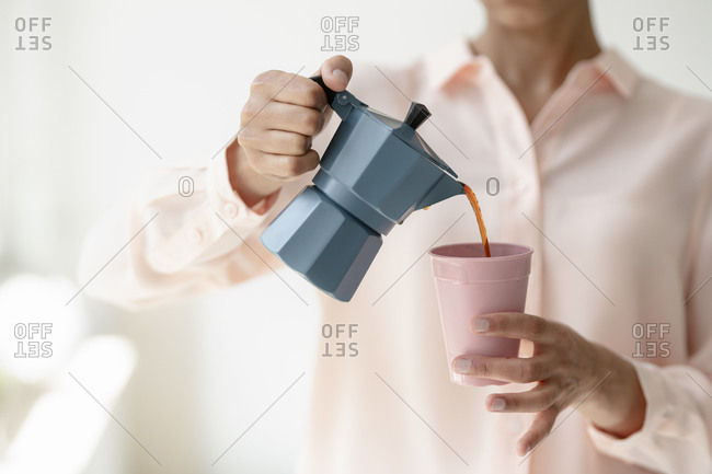Close-up of woman pouring coffee into cup