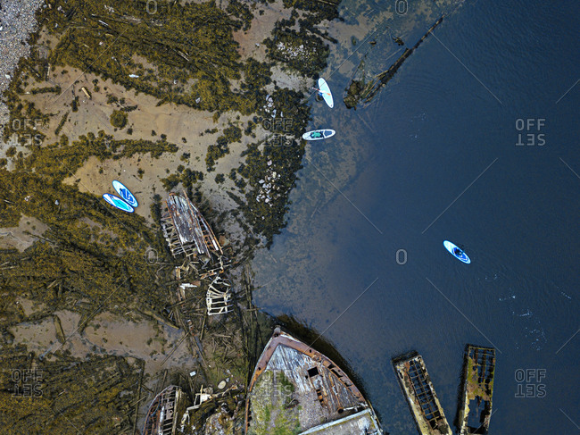 Russia- Murmansk region- Kolsky District- Teriberka- Sup surfer near shipwrecks on Barents Sea coast- aerial view