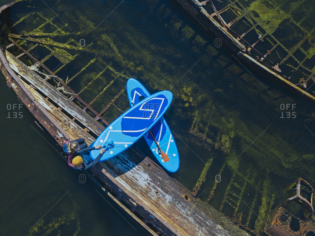 Russia- Murmansk Oblast- Kolsky District- Teriberka- Couple of sup surfers sitting on shipwreck on Barents Sea- aerial view