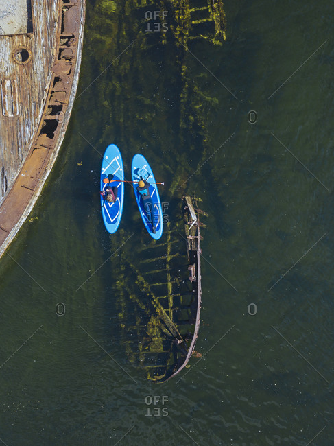 Russia- Murmansk Oblast- Kolsky District- Teriberka- Couple of sup surfers near shipwrecks on Barents Sea- aerial view