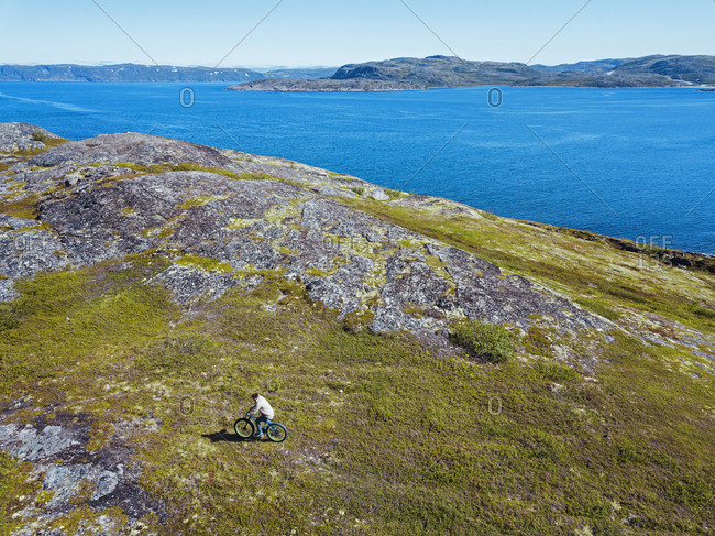 Russia- Murmansk region- Kolsky District- Teriberka- Man cycling on coastline- aerial view