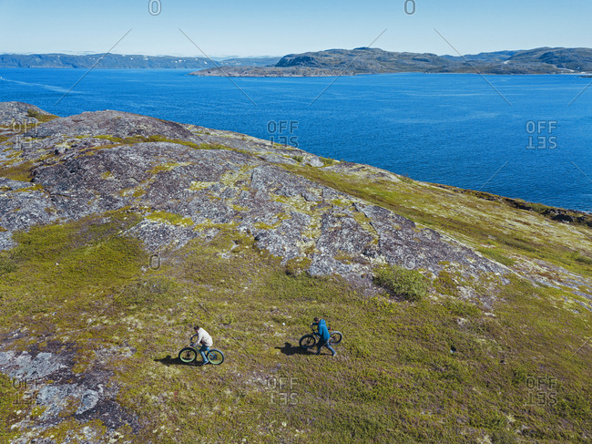 Russia- Murmansk region- Kolsky District- Teriberka- Two men with bicycles on coastline- aerial view