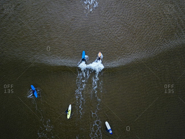 Aerial view of people surfing in brown waters of Barents Sea