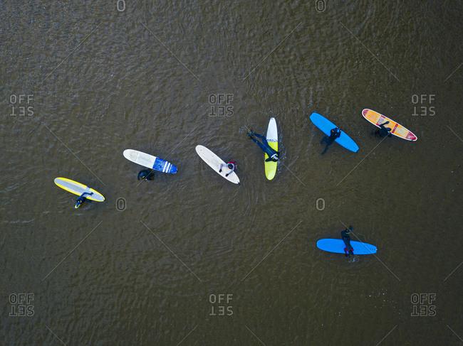 Aerial view of people surfing in brown waters of Barents Sea