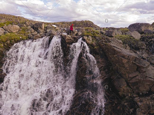 Russia- Murmansk Oblast- Teriberka- Aerial view of female hiker walking at edge of splashing waterfall