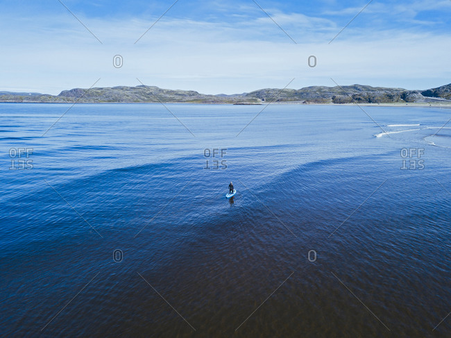 Aerial view of young woman surfing in blue waters of Barents Sea