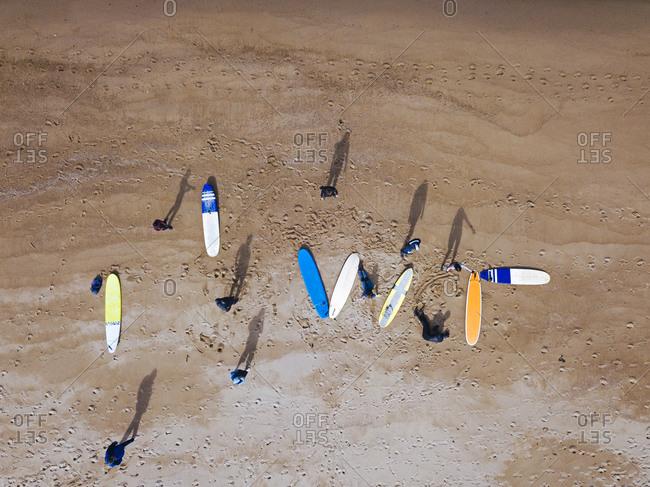 Aerial view of surfers preparing at sandy coastal beach
