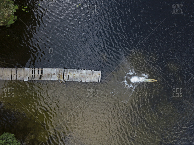 Aerial view of young man splashing in lake