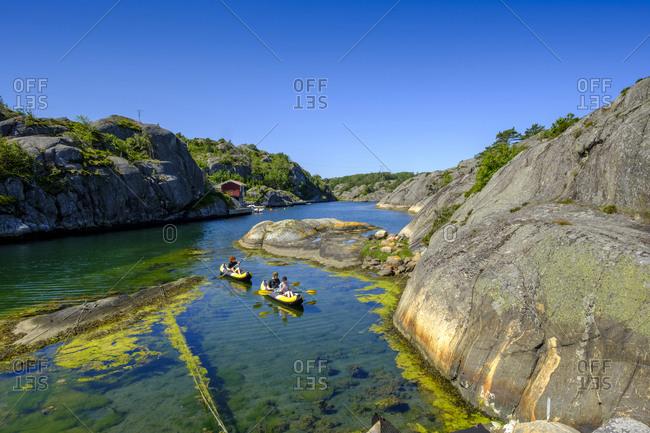 People kayaking across rocky inlet in summer