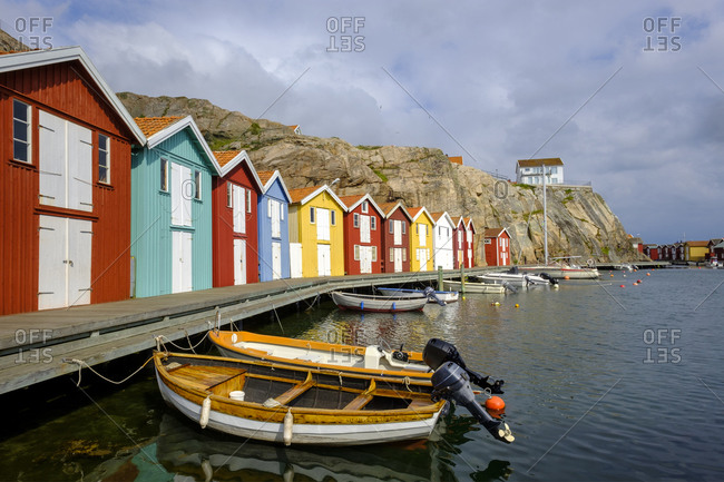 June 17, 2019: Sweden- Vastra Gotaland County- Smogen- Boats moored in front of colorful boathouses