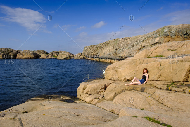 Teenage girl relaxing on rocky shore in summer