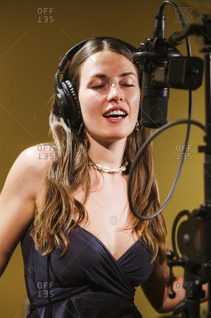 Singer with headphones at microphone in recording studio