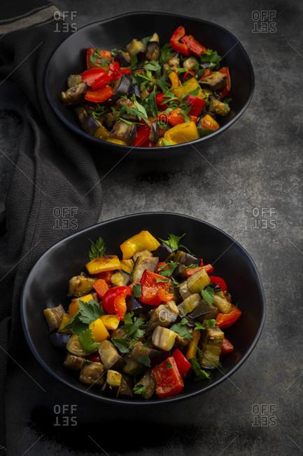 Two bowls ofstir-friedvegan salad with eggplants- paprika and parsley