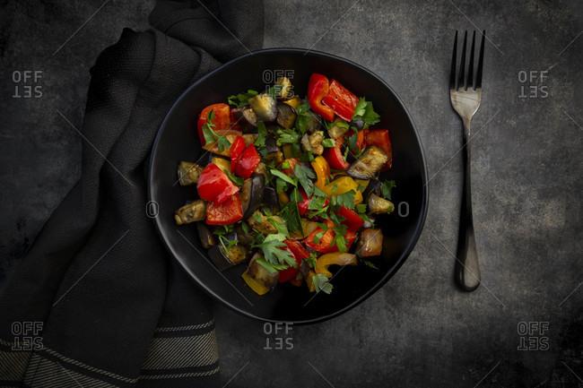 Bowl ofstir-friedvegan salad with eggplants- paprika and parsley
