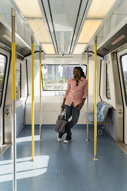 Afro young man with bag standing in train- Miami- Florida- USA