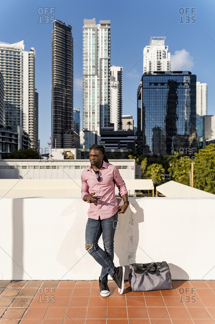 Afro young man holding smart phone standing against skyscrapers in Miami- Florida- USA