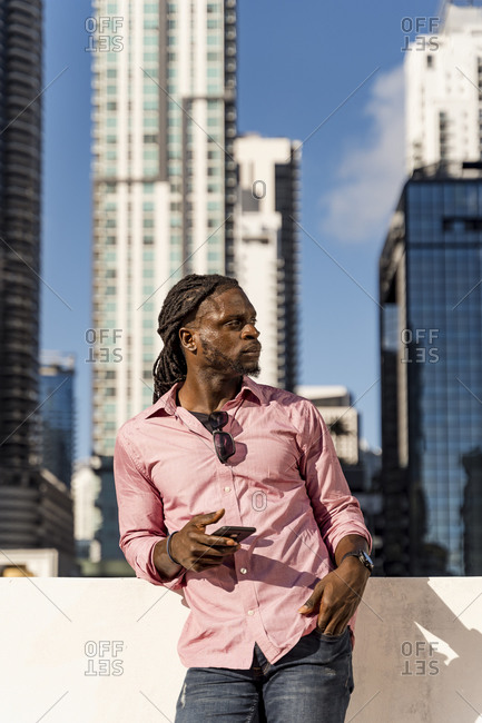 Afro young man holding smart phone looking away while standing against skyscrapers in Miami- Florida- USA