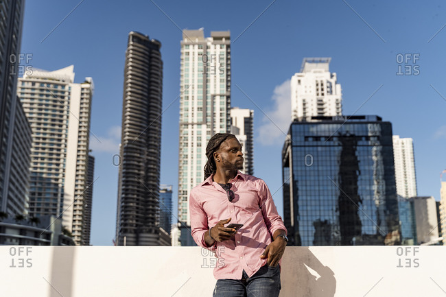 Thoughtful afro man holding smart phone standing against skyscrapers in Miami- Florida- USA