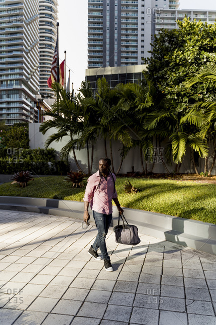 Afro young man with bag walking on footpath in Miami city- Florida- USA