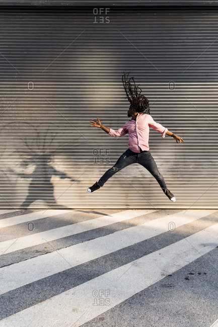 Afro young man with dreadlocks jumping on street against wall