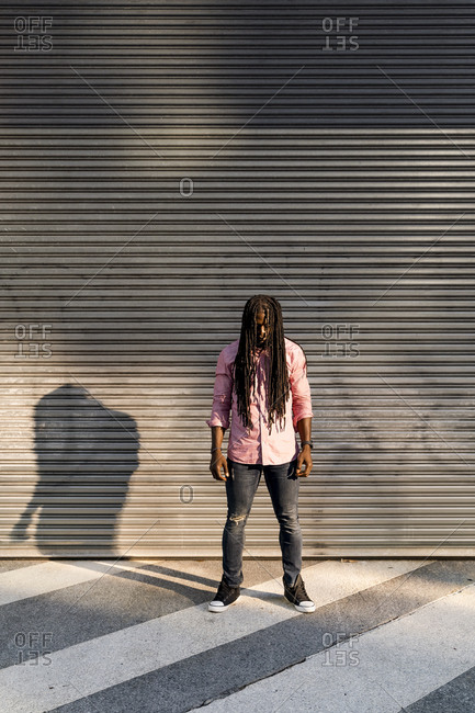 Afro young man with dreadlocks standing on street against wall