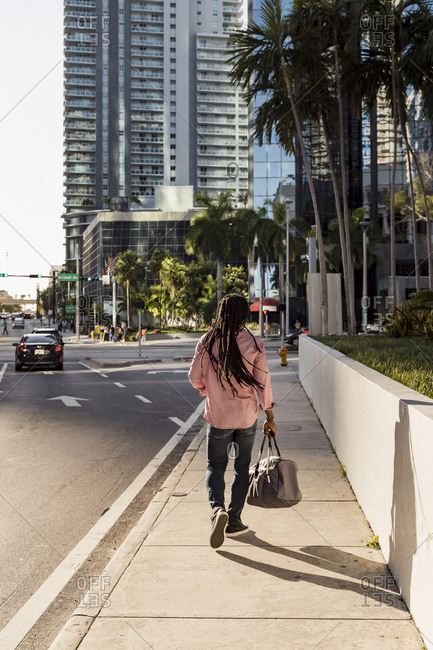 Afro man with dreadlocks holding bag while walking on sidewalk in Miami city- Florida- USA