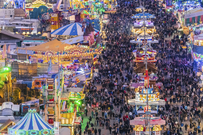 May 29, 2020: Germany- Bavaria- Munich- Drone view of crowds of people celebrating Oktoberfest in vast amusement park at dusk