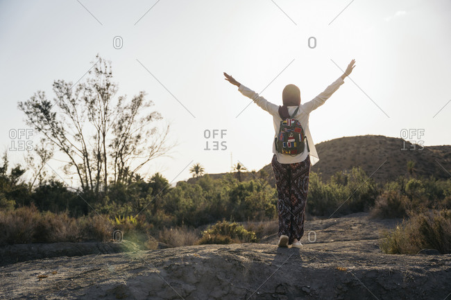 Young tourist woman wearing Hijab standing in desert landscape with raised arms