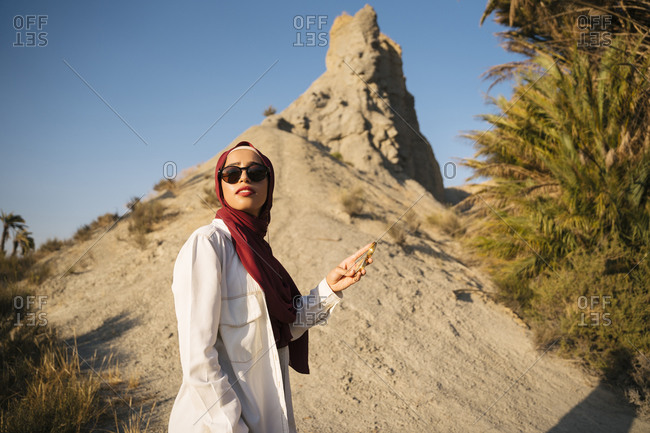 Young tourist woman wearing Hijab holding compass