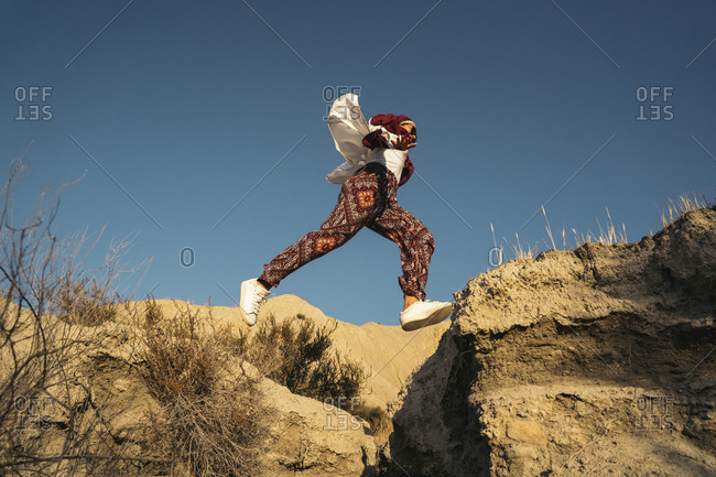 Young tourist woman wearing Hijab jumping over a gap