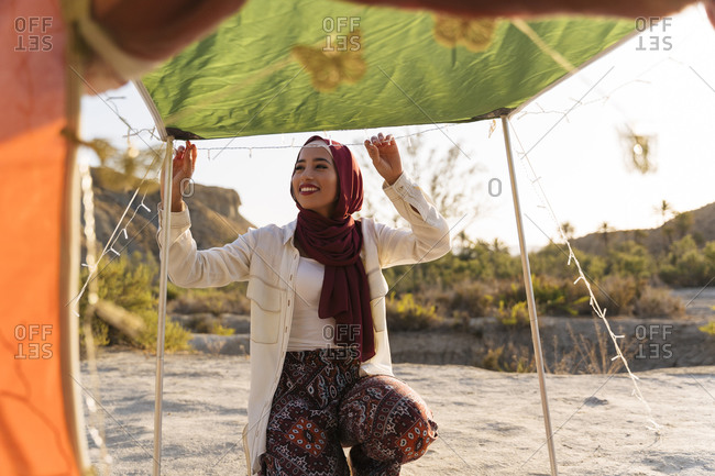 Smiling young tourist woman wearing Hijab decorating a tent