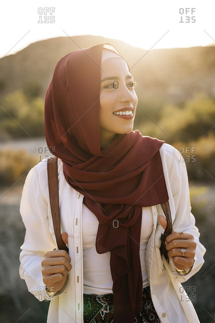 Smiling young tourist woman wearing Hijab in desert landscape looking around