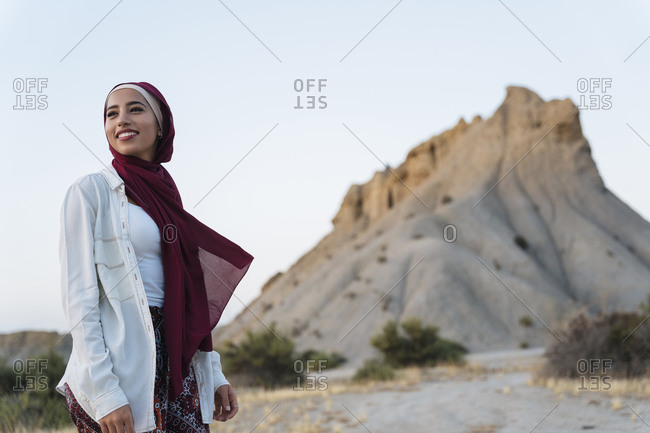 Smiling young tourist woman wearing Hijab in desert landscape