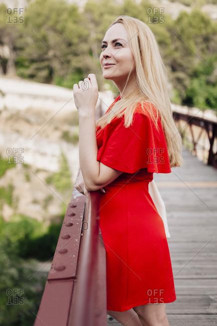 Smiling woman looking up standing on Saint Paul Bridge in Cuenca- Spain