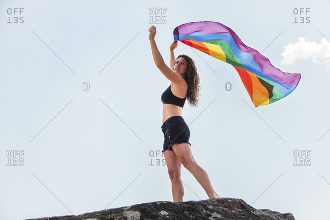 Mid adult woman waving rainbow flag while standing on rock against sky