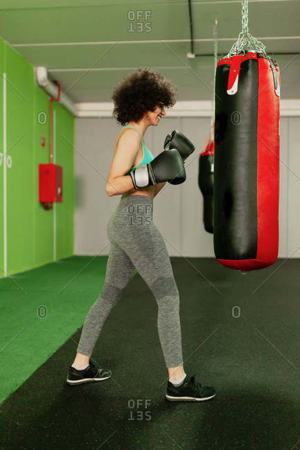 Female boxer practicing with punching bag in health club