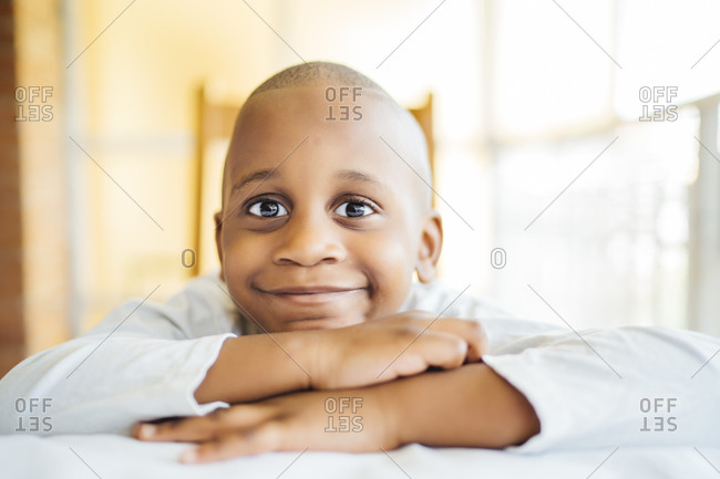 Close-up of smiling boy with shaved head leaning on table at home