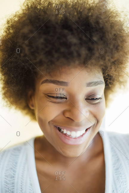 Close-up of smiling woman with afro hair looking down at home