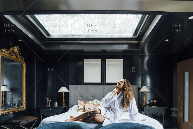 Mid adult woman looking through skylight while relaxing on bed in hotel