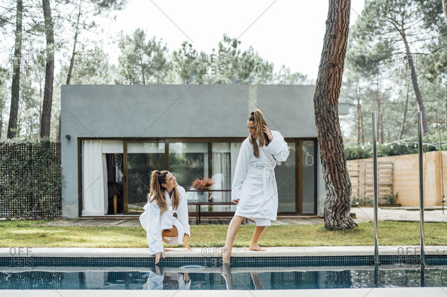 Happy twin sisters touching water of swimming pool at tourist resort
