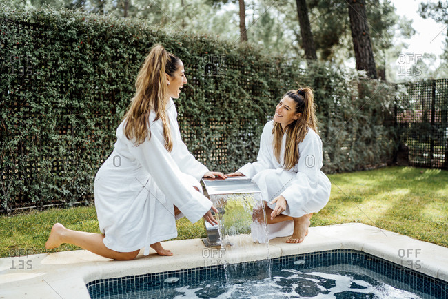 Cheerful twins sisters kneeling by fountain at poolside in tourist resort