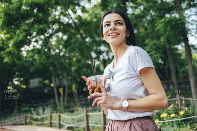 Smiling young woman holding soft drink looking away while standing against trees in park