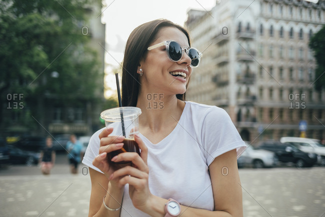 Cheerful beautiful woman wearing sunglasses holding soft drink while standing in city