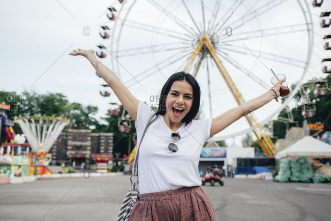 Carefree young woman with arms raised standing at amusement park