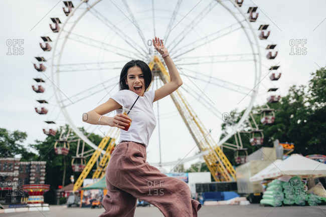 Young woman holding soft drink cup dancing against Ferris wheel in amusement park