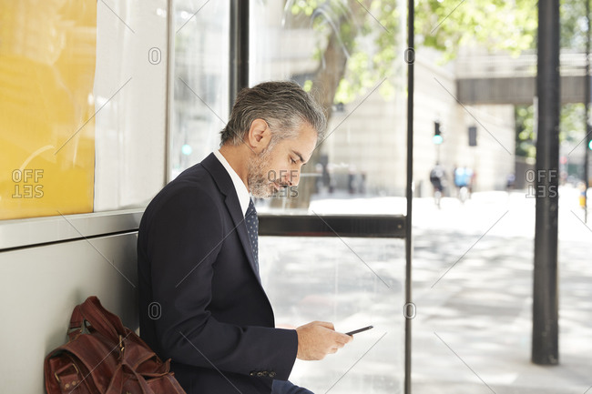 Businessman using phone while sitting at bus stop