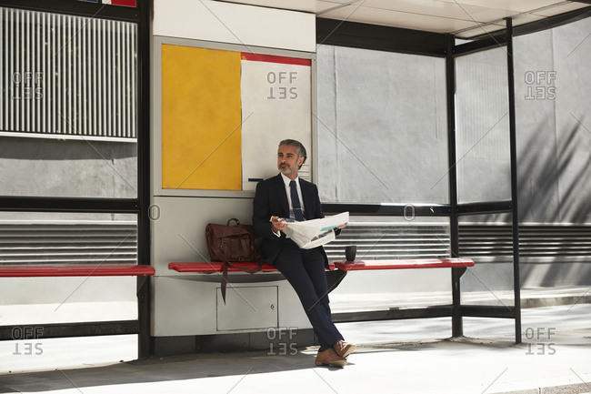 Businessman with newspaper waiting at bus stop