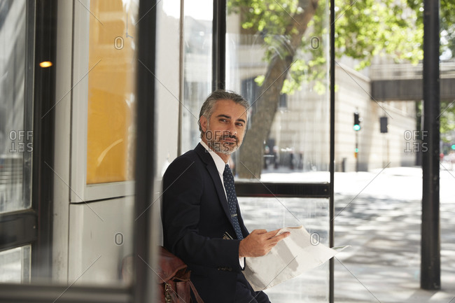 Confident businessman with newspaper waiting at bus stop
