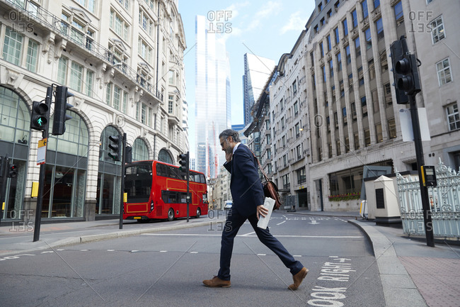 Businessman talking on smart phone while crossing road in city